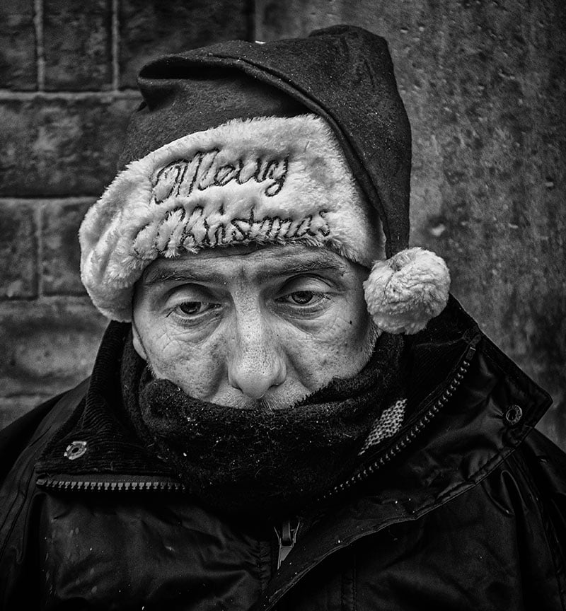Homeless man with Merry Christmas hat