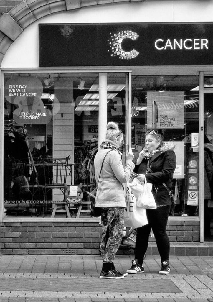 women smoking outside cancer research charity shop