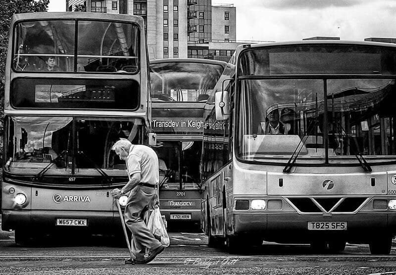 Old man walking in front of buses, Leeds