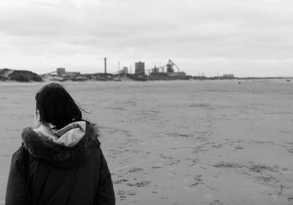 girl on Redcar beach with steel works in distance