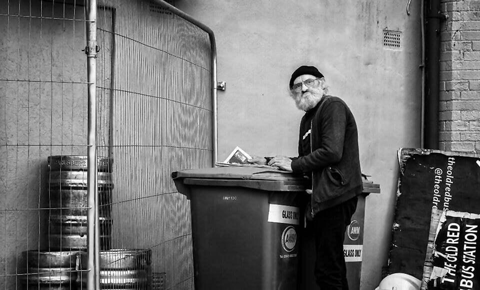 Man reading near garbage bins, Leeds